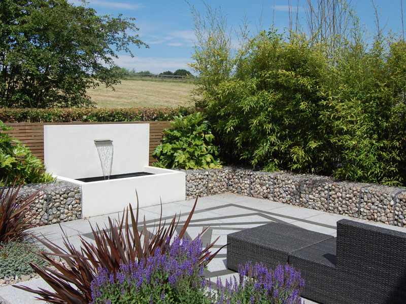 Contemporary garden with cedar battens, gabions filled with cobbles and a stainless steel water blade