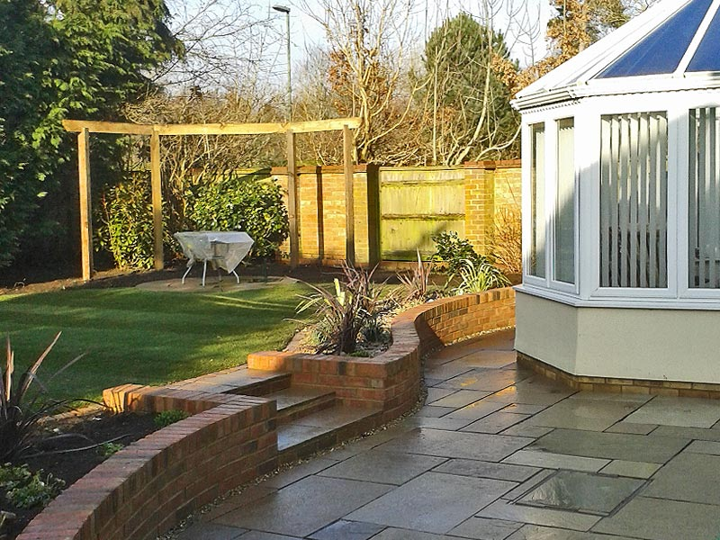 The lower patio leads up to a raised level lawn with stone circle paving framed by an arbout rail