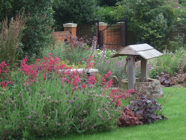 Relaxed perennial planting surrounds a restored well