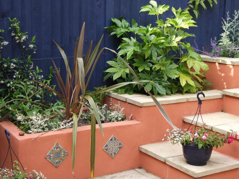 Lush planting in built-in painted planters set off by a deep blue fence