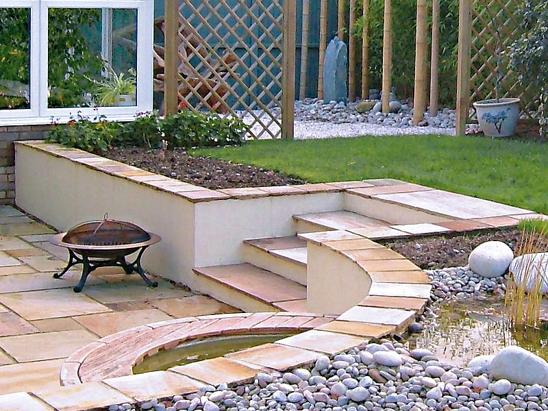 Sunken patio with cream rendered walls and water feature