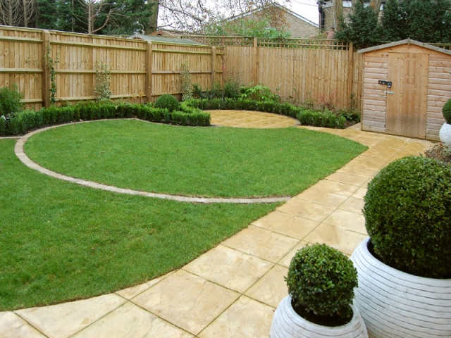 Small back garden with circular lawns and box edging