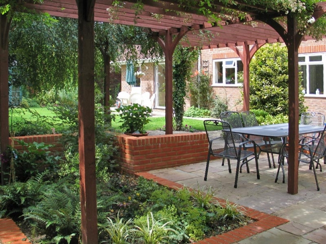 Shady sunken patio with brick edging framed by a pergola
