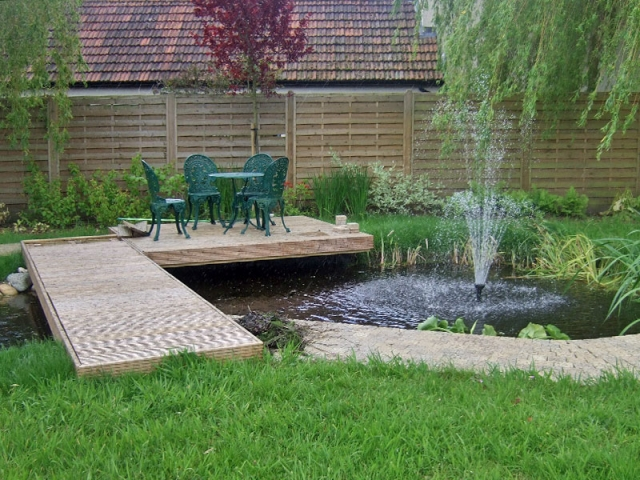 Medium pond with fountain and decking bridge and seating area