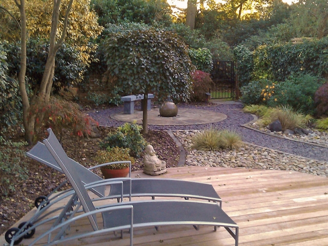Enclosed garden with decking, slate paths and a circular patio and spherical water feature