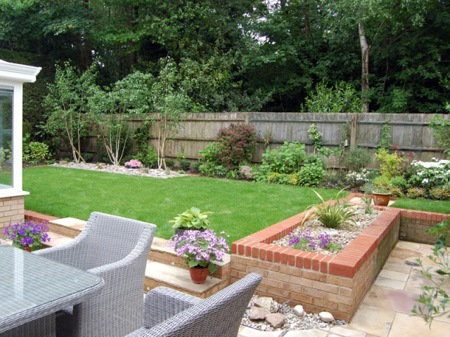 Sunken patio, raised lawn and trio of silver birches