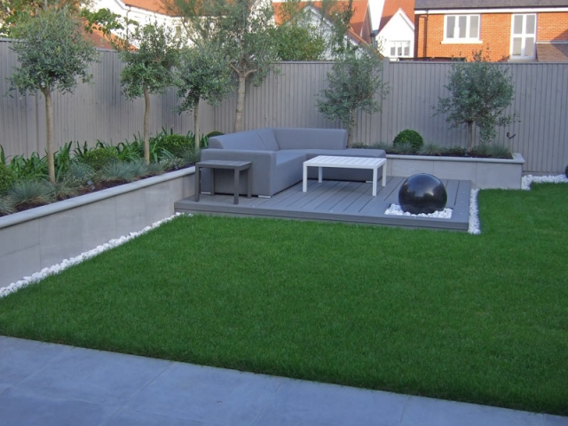 Central lawn with decked seating area, water feature and raised planting beds