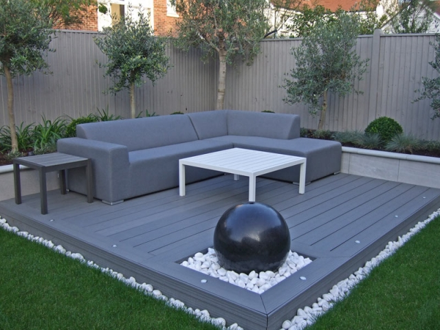 Contemporary outdoor lounge with composite decking and spherical granite water feature in constrained palette of greens and grey