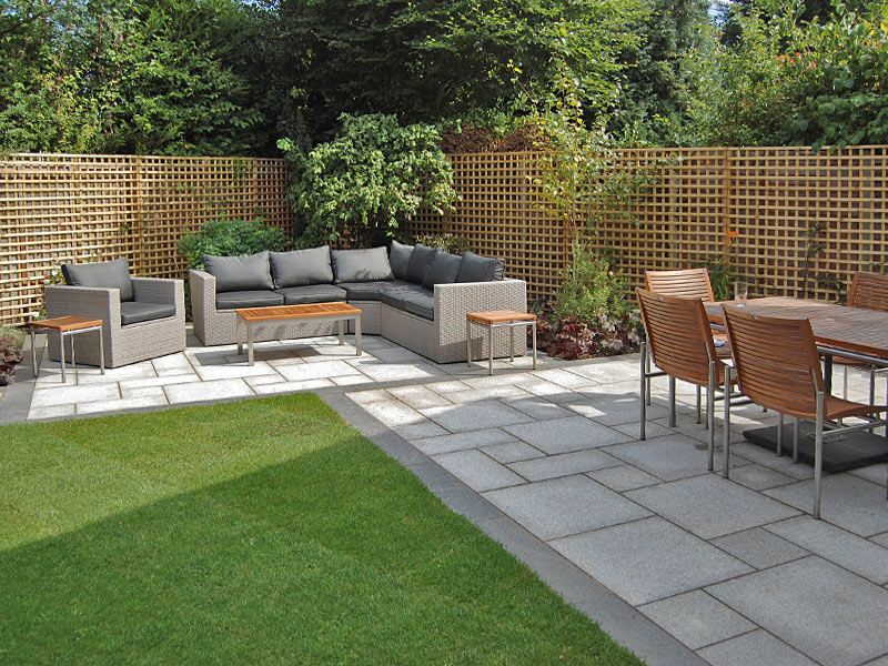 Outdoor lounge and dining areas with trellis boundary and granite paving