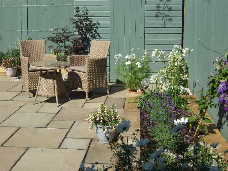 Contemporary small back garden with painted timber