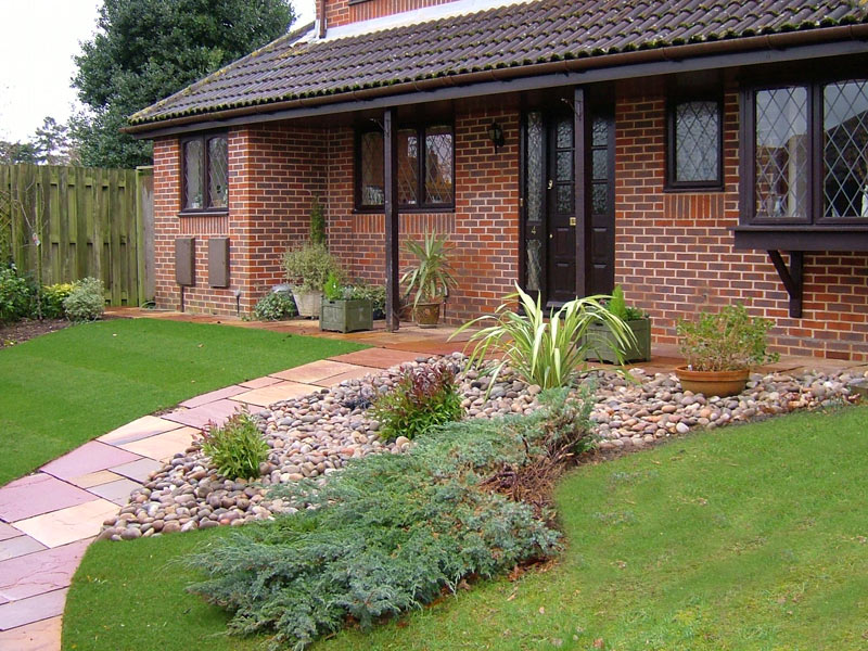 Front garden with modak sandstone path and planting through cobbles.