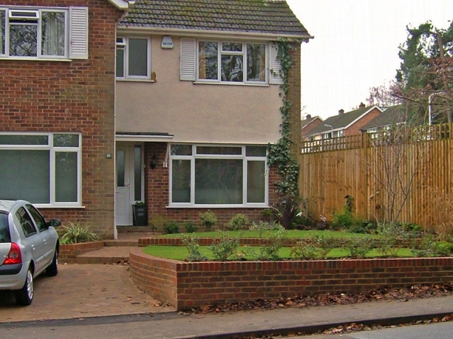 Curving brick terraces with steps to front door