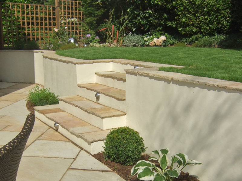Rendered wall with riven sandstone steps and lighting