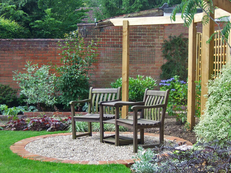 Traditional garden with small gravel seating area framed by an arbour rail