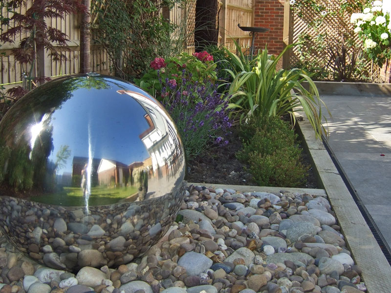 Stainless steel sphere recycling water feature reflects the surrounding garden