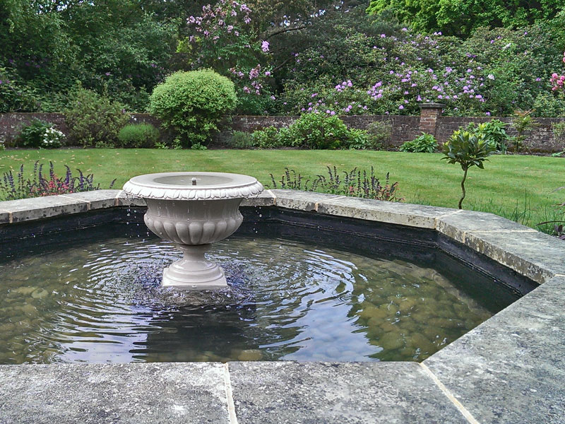 Traditional formal pool with central floating urn