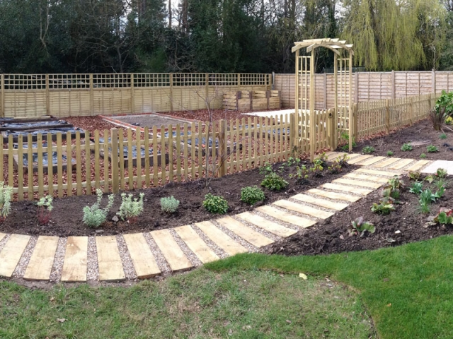 Sleeper path to vegetable garden with arched entrance