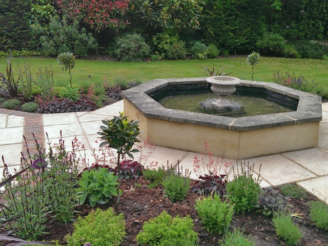 Octagonal formal pool with central floating urn and planting