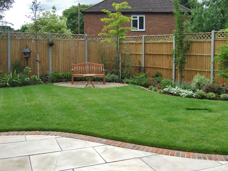 Traditional garden with brick edged patio and curving borders