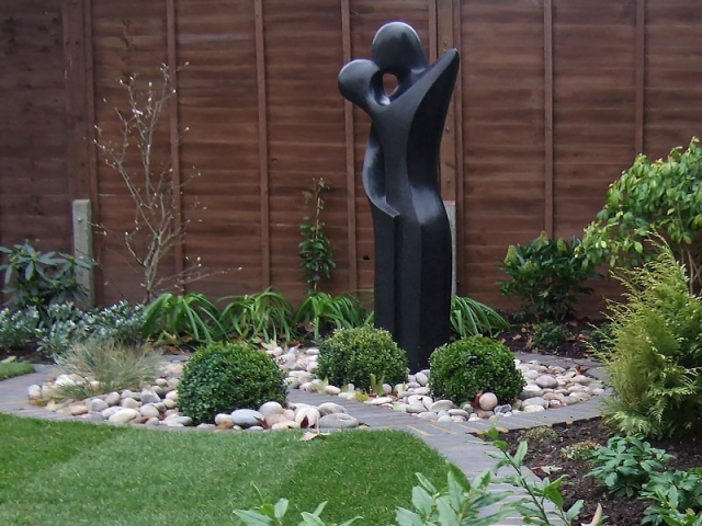 Contemporary statue set in a circular bed with pebbles and Box Balls