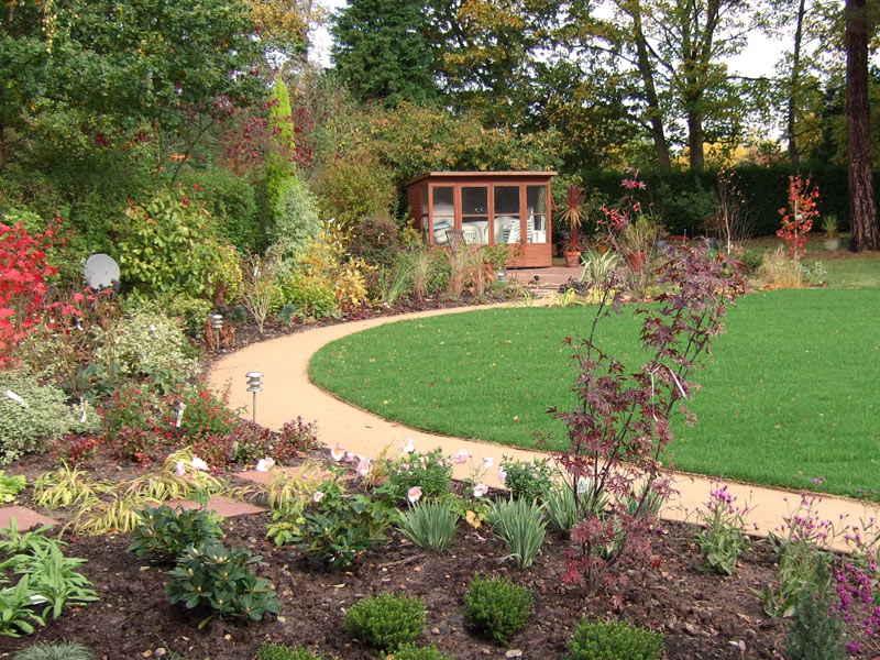 Deep mixed borders and sel-binding gravel path surround a central lawn