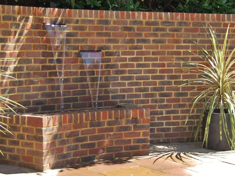 Recycling water feature with two stainless steel water blades set into brick wall