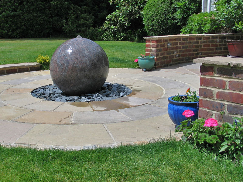 Large stone sphere water feature as focal point in circular patio