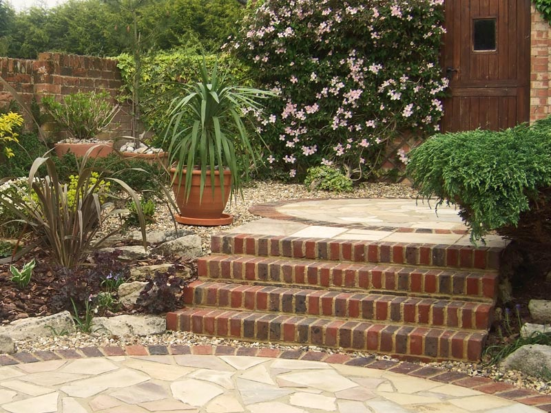 Brick steps and crazy paving with gravel surrounds and planting