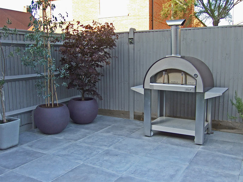 Grey porcelain paving with stainless steel pizza oven and large Cadix planters