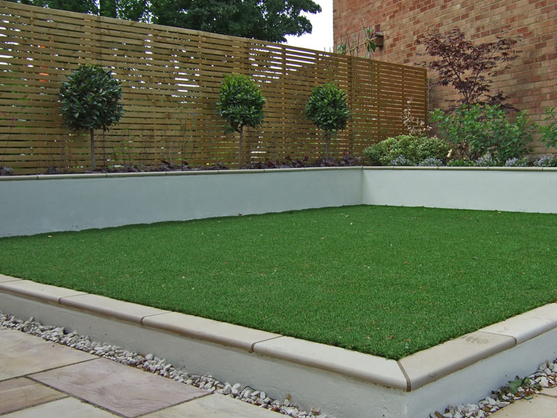 Contemporay garden with horizontal slatted fence and artificial grass