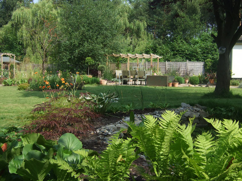 Large country garden with pond, pergola and borders