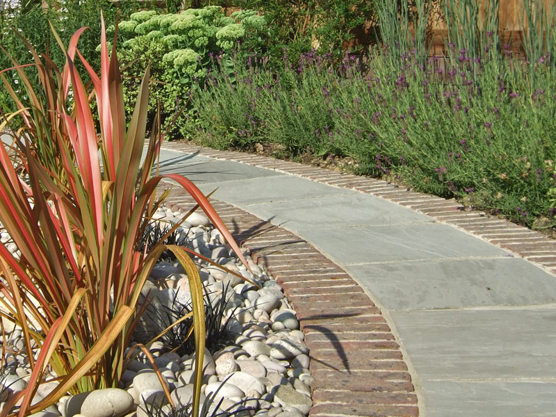 Curved sandstone path with red brick edging