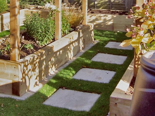Stepping stone path through grass between sleeper raised beds