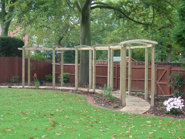 Long bow topped pergola over curving walkway